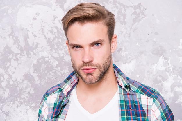 Macho człowiek tło grunge. męska kolekcja wiosenna moda. charyzmatyczna koszula studencka w kratę. nieogolony mężczyzna dba o swój wygląd. koncepcja fryzjera. męskie zmysłowość portret. seksowny facet w stylu casual.
