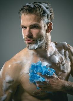 Macho mycie gąbką mężczyzna z brodą jest mytą gąbką do ciała atrakcyjnie wyglądający młody mężczyzna
