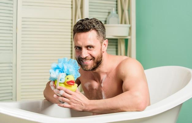 Macho z gąbką kąpie się w domu. kąpiel z mydłem. rutyna urody. koncepcja relaksu i zabawy. codzienna kąpiel pomaga pokonać depresję. przystojny muskularny mężczyzna relaksująca wanna z żółtą kaczką.