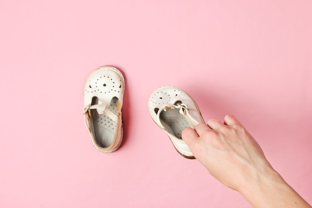Macierzyństwo, koncepcja dzieciństwa. kobiece ręce trzymając dziecięce skórzane sandały na różowo.