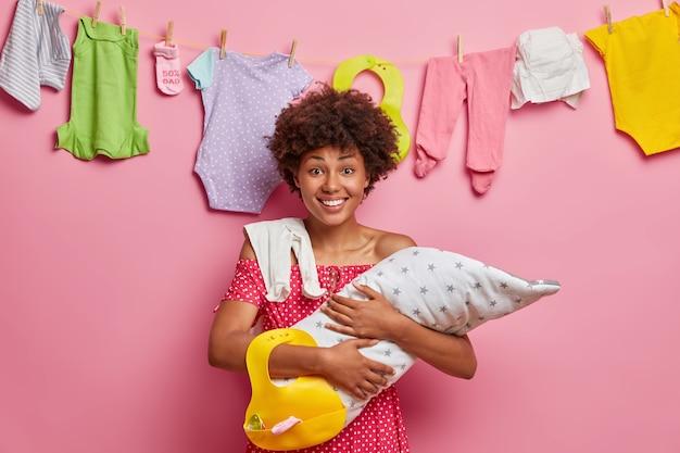 Macierzyństwo, rodzicielstwo, koncepcja opieki nad dzieckiem. szczęśliwa młoda matka niesie dziecko na ramionach, trzyma śliniaczek, pozuje