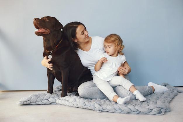 Macierzysta i mała córka bawić się z psem w domu