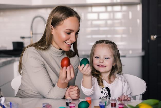 Macierzysta i mała córka z easter jajkami i easter koszem w kuchni przygotowywającej dla wielkanocy