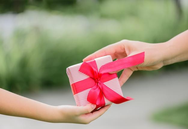 Macierzysta ręka daje prezenta pudełku jej dziecko. wakacje, teraźniejszość, boże narodzenie