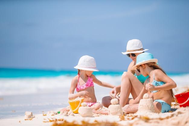 Macierzyste i małe córki robi piaskowi roszować przy tropikalną plażą