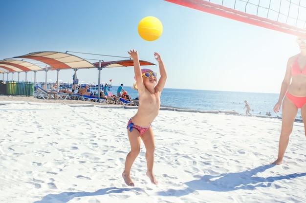Macierzysty bawić się z jej małą śliczną córką przy plażą