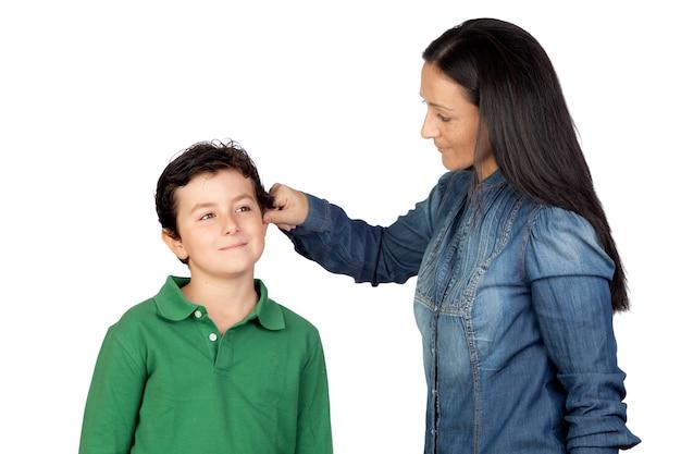 Macierzysty ciągnięcie jej dziecko ucho dla być niegrzeczny odosobniony na białym tle