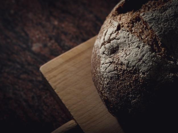 Macierzysty ciasto chleb na drewnianej desce.