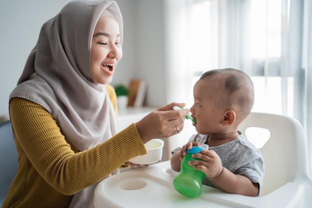 Macierzysty karmienie jej chłopiec podczas gdy siedzący na wysokim krześle