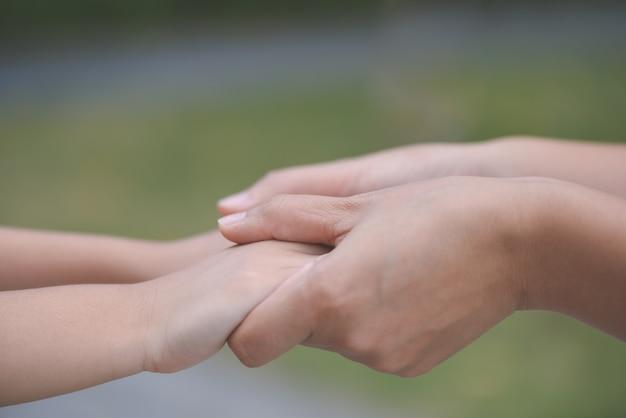 Macierzysty mienie ręka jego syn z zielonego szkła tłem. miłość, rodzina i dzień matki