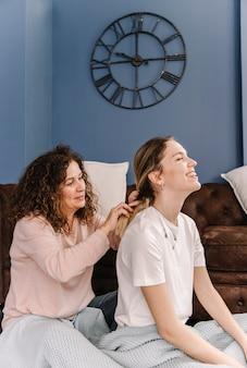Macierzysty splata włosy uśmiechnięta córka