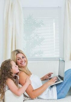 Macierzysty używa notatnik podczas gdy patrzejący jej córki