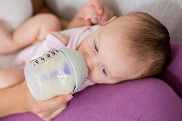 Macierzysty żywieniowy dziecko z dojną butelką w żywym pokoju