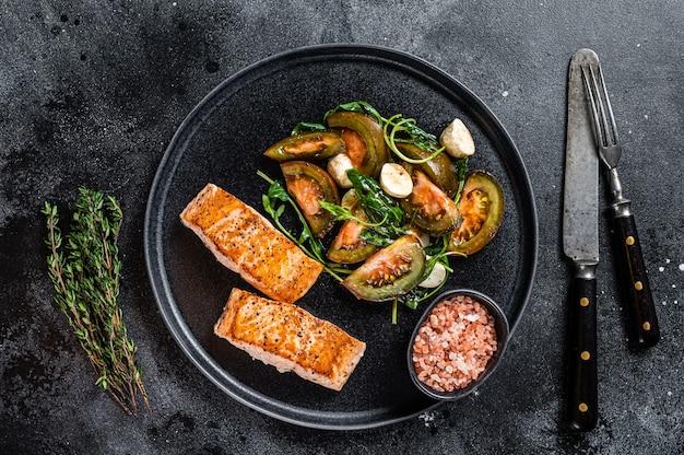Mączka rybna z pieczonymi stekami z polędwicy z łososia i sałatką z pomidorów z rukoli na talerzu