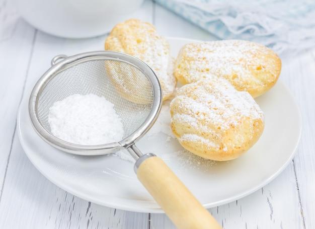 Madeleines w proszku w cukrze na białym stole