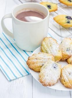 Madeleines w proszku w cukrze z jagodami i gorącą czekoladą