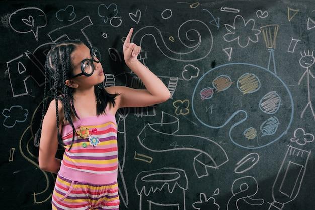 Mądra mała dziewczynka uśmiechając się przed tablicą