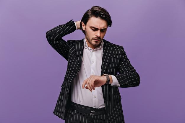 Mądry, atrakcyjny mężczyzna z brunetką, białą koszulą i modnym prążkowanym garniturem, patrzący na zegarek na dłoni