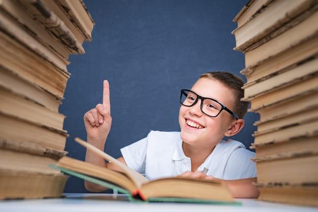 Mądry chłopiec w okularach siedzi między dwoma stosami książek i patrzy w górę, wskazując palcem