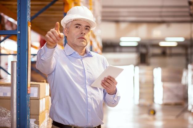 Mądry, doświadczony kierownik logistyki korzystający z tabletu w pracy