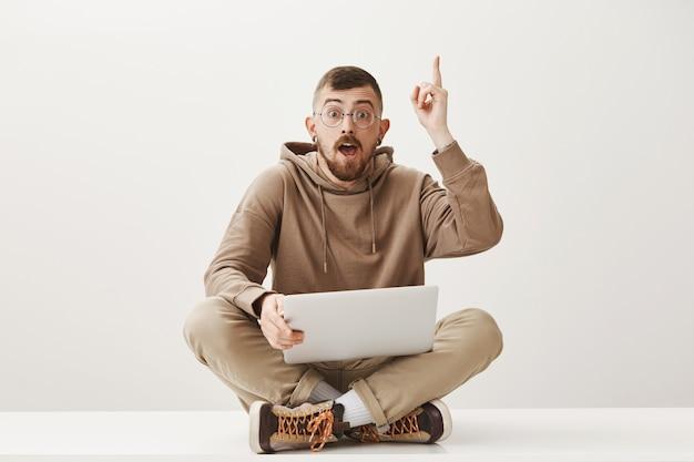 Mądry facet siedzi z laptopem, ma świetny pomysł, dzieli się sugestiami