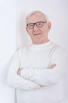 Mądry i pewny siebie. pewny siebie starszy mężczyzna trzymający skrzyżowane ręce i uśmiechający się do kamery, opierając się o ścianę