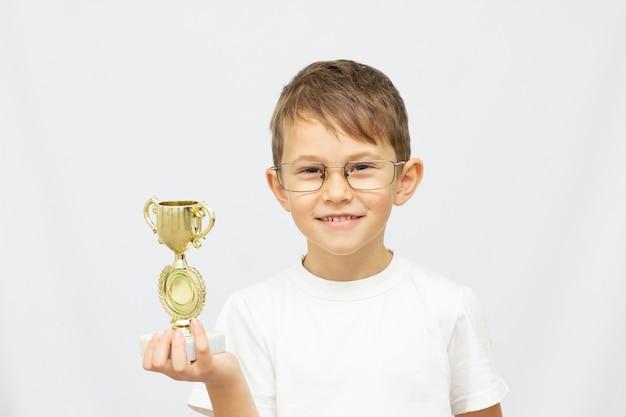 Mądry mały chłopiec świętuje swoje zdobyte złote trofeum pod ścianą. koncepcja inteligentnych dzieci