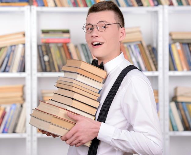 Mądry mężczyzna zabrał wiele książek w bibliotece.