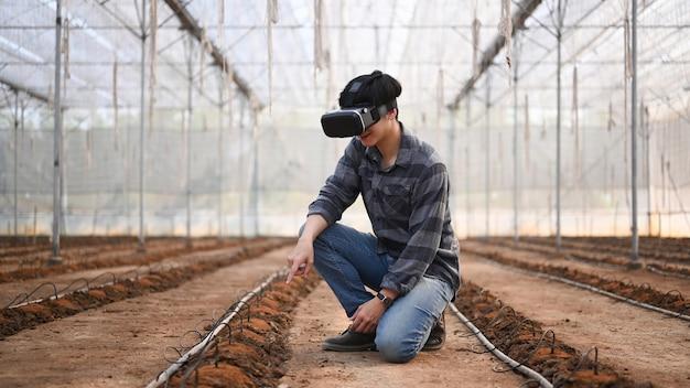 Mądry rolnik noszący okulary rzeczywistości wizualnej lub technologię vr siedząc w szklarni.