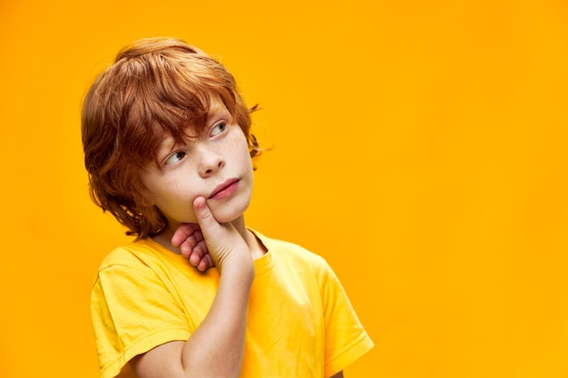 Mądry rudowłosy chłopiec dotyka dłonią twarzy i spogląda w bok