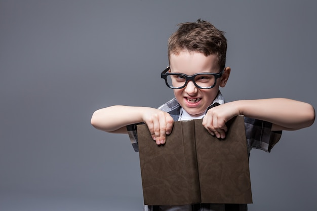 Mądry uczeń w okularach z podręcznikiem w rękach