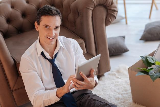 Mądry. Wesoły, Mądry, Entuzjastyczny Mężczyzna Siedzi Na Podłodze Obok Fotela I Wygląda Na Szczęśliwego, Trzymając W Rękach Nowoczesny Tablet Premium Zdjęcia