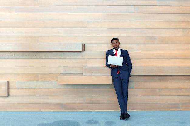Mądrze afrykański biznesowy mężczyzna używa laptop w biurze