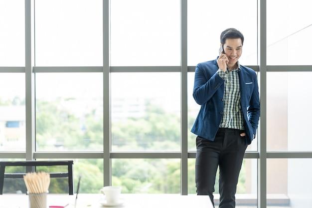 Mądrze azjatycki biznesowy mężczyzna mówi używać smartphone.