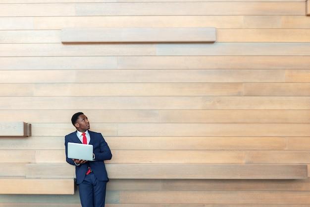 Mądrze biznesowy afrykański mężczyzna używa laptop w biurze. copyspace