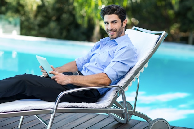 Mądrze mężczyzna używa cyfrową pastylkę blisko basenu