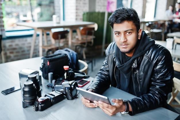 Mądrze młody azjatykci mężczyzna fotograf pracuje z pastylką podczas obsiadania przy kawiarnią