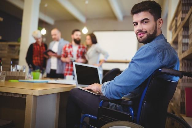 Mądrze niepełnosprawny biznesmen używa laptop przy biurkiem