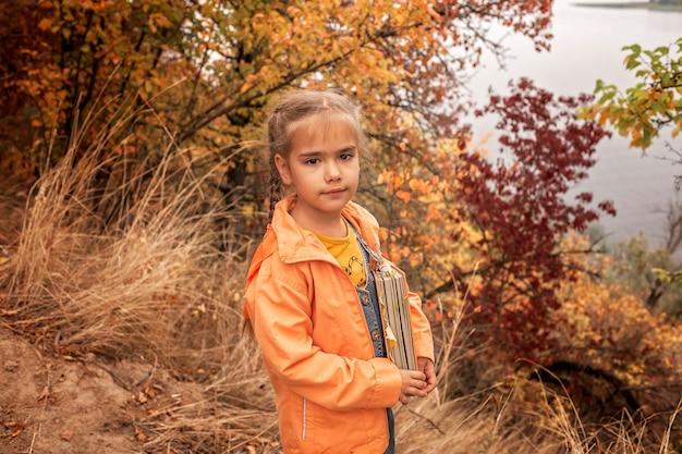 Mądrze śliczna dzieciak dziewczyna trzyma książkę z suchymi żółtymi liśćmi