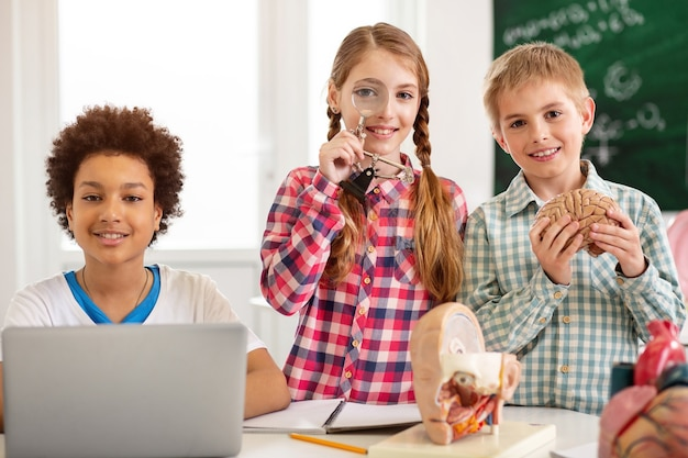 Mądrzy studenci. szczęśliwi inteligentni uczniowie, którzy patrzą na ciebie podczas zajęć z biologii
