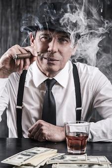 Mafia nie śpi. poważny starszy mężczyzna w koszuli i szelkach siedzi przy stole i pali cygaro, podczas gdy obok niego leży mnóstwo pieniędzy