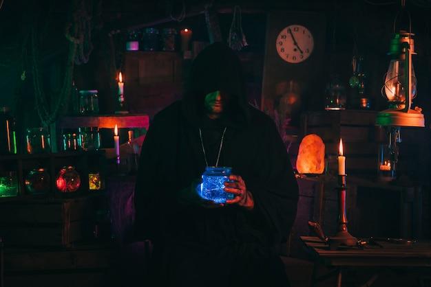 Mag alchemika trzyma w rękach butelkę z mistyczną miksturą. sorcerer jest wiedźminem w mrocznym strasznym laboratorium