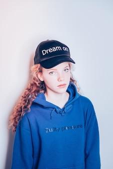 Magazyn dla nastolatków. kręcona dziewczyna o jasnozielonych oczach patrząca prosto w kamerę podczas noszenia ubrań z mody ulicznej