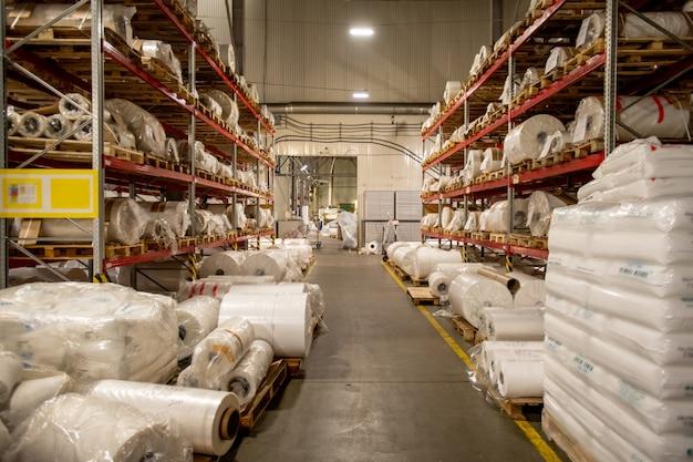 Magazyn dużej nowoczesnej fabryki chemicznej z regałami rolowanych i pakowanych cewek folii polietylenowej