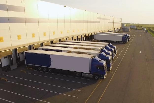 Magazyn dystrybucyjny z ciężarówkami oczekującymi na załadunek
