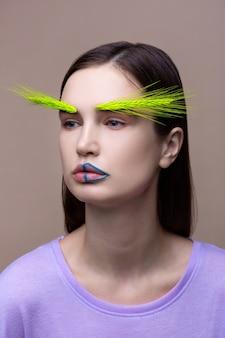 Magazyn ekologiczny. nowoczesna młoda modelka pozuje do magazynu ekologicznego z kolcem na twarzy