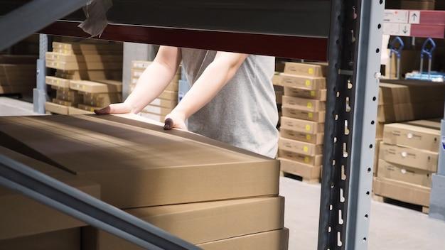 Magazyn o dużej pojemności magazynowej lub logistycznej lub ładunkowej do dystrybucji. a ręka mężczyzny podnosi pudełko.