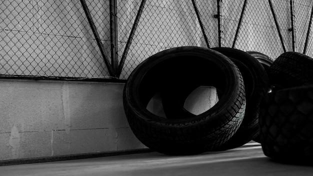 Magazyn opon. cztery opony na betonowej podłodze. na ścianie czarna siatka. brutalne zdjęcie