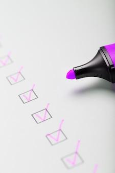 Magenta znacznik ze znacznikami na arkuszu kontrolnym. lista kontrolna zrealizowanej koncepcji zadania.