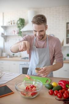 Magia kuchni. mężczyzna dodający przyprawy do sałatki warzywnej